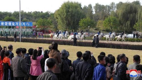 Hàng trăm khán giả đã tới xem và dùng điện thoại ghi hình lại khi những chú ngựa màu xám trắng và những tay đua bắt đầu vào cuộc. Ảnh: KCNA.